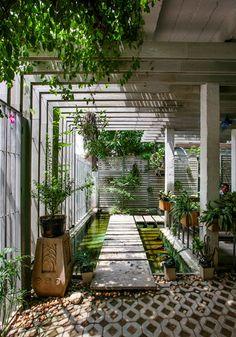 Un patio ombragé auquel on accède via un pont sur l'eau signe l'arrivée vers la maison.