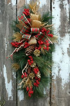 Fresh Christmas door swag wreath. This stunning design is the perfect festive welcome for any door. Made with top quality fresh foliage and simple decorations. Natural pine cones and fresh red berries finished with gold and red ribbon bows. Approx. 2ft in length. Colours can be changed to suit, white and silver, white and blue.
