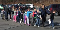 A gunman entered Sandy Hook Elementary School on December 14, 2012, and killed six staffers and 20 first-graders before turning the gun on himself. In this image a Connecticut State Police officer leads children out of the school — in Newtown, Connecticut.  Photo credit: Shannon Hicks