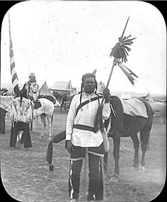 "Early 1900's Notes 	Curley next to horse and two other Crow men behind him in Montana. One holds American flag. Tipi and building in background.  Hand written on edge of slide, ""Curley - Crow Scout with Custer in Battle, June 1876. Sole survivor of Custer's immediate group. Custer is supposed to have told him to leave."""