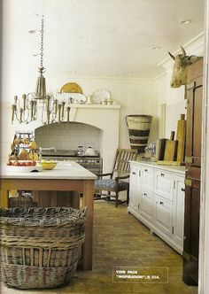 Here is a fabulous Country French kitchen ! Complete with terra cotta flooring, a marble top farm table, white ironstone, tart boards, a bottle drying rack, bull's head, vineyard hopper and woven baskets.