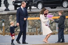 George's mother is more receptive and gratefully receives a bouquet of flowers from nine-year-old schoolboy Daniel as she holds Princess Charlotte in her arms