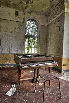 abandoned piano in empty room.
