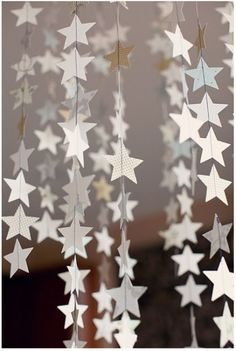 "DIY Hanging Stars - we can do these slightly differently (larger stars (~4""), fewer per garland, double the stars so don't see string) hanging from light boxes in main room. kite string is about right weight. light weight card stock - cream on cream print?"