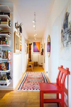 Konst på väggarna och en vacker kelimmatta på golvet i hallen. Den röda stolen är Johan Kandells Pimpim och pallen i fonden en av Ray och Charles Eames afrikanskt inspirerade.