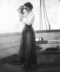 A woman on the deck of a ship at sea taking a sight with a sextant.