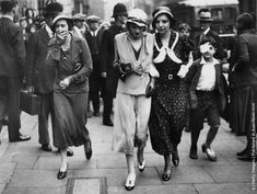 """Actress, drug addict and """"It Girl"""" Brenda Dean Paul (1907–1959, centre) leaves court after facing drugs charges, July 1933. She is holding a tin of large Sub Rosa cigarettes."""