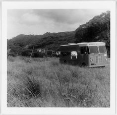 Ref: PA1-o-848-36-2 Country Library Service bookvan encampment somewhere between Kiritehere and Whareorino, Waitomo District. The driver has hung his washing out on a line, one end of which is attached to the van. Photographed by James Hector Sutherland in the 1970s