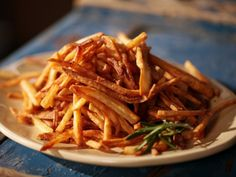 Take it from Michael Symon: There's no better way to ensure crispy fries than to fry them twice. After the initial dip, it takes just 5 minutes to finish the fries off at a higher heat. Don't forget to add a final flourish of flaky sea salt and chopped rosemary.