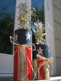 "Fourth of July Firecracker  Very simple- cut a garden round post to desired height;   Mine are 8"" with 3 1/2"" of blue &   11"" with 4"" blue   Paint your stripes and stars (4) I rough paint so it is rustic looking.   Glue ribbon or raffia. Drill hole on the top and add your sparkles!   Great Holiday sparkle and easy D I Y  These have been a great hit as gifts for partys with family and friends!"