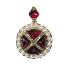 A Victorian garnet, pearl and diamond pendent, set to the centre with four triangular cabochon-cut garnets between rose-cut diamond-set cross and natural pearl surround, with cabochon-cut garnet and rose-cut diamond loop, all set in a yellow gold mount with brooch fittings and locket, circa 1860.