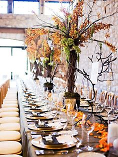 Tall centerpiece trees, orange rose petals and candles a-tuscan-wedding