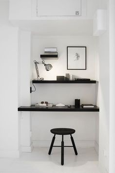 Black floating shelves on white walls create a modern office nook in a Swedish apartment