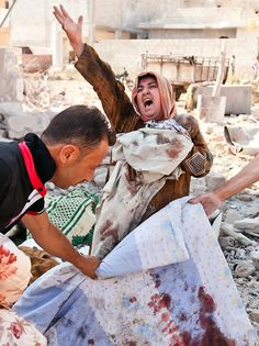 Una mujer sostiene a su bebé al tiempo que llora al ver el cadáver de su esposo, fallecidos en un bombardeo aéreo del ejército Sirio en Azaz, a 47 km al norte de Alepo - Vedat Xhymshiti