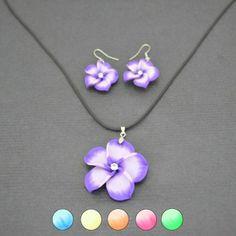 """Cette très jolie parure est composée d'un collier fantaisie cordon avec pendentif en """"soft ceramic"""" et des boucles d'oreilles avec ces mêmes fleurs des îles."""
