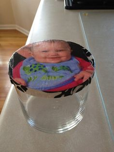 I used an old candle jar from Bath & Body Works for this one.  Mod Podge fabric and photo on top.  Makes a great gift.