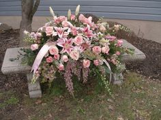 """A classic, feminine, casket spray to epitomize the love and memories of a dear lady. The design features roses, larkspur, heather, oriental lilies and so much more in this featured closed casket spray. We also offer a """"half-couch"""" design where the lid is open over the upper torso and closed over the lower part: the """"half-couch"""" spray is placed on the closed part of the lid. Floral selection may vary depending upon design chosen, season and market availability. The full len..."""