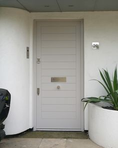 Strikingly modern black front door with fanlight and distinctive chrome door furniture. This imposing recessed entrance benefits from a contemporary twist. Contemporary, Faux Wood Garage Door, Modern Front Door, Contemporary Front Doors, Wood Garage Doors, Grey Front Doors, Modern, Garage Door Types, Exterior Doors