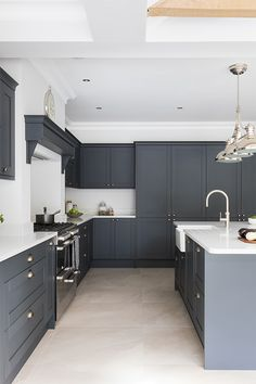 Create a dark grey shaker kitchen with white worktops to create a dark contemporary kitchen. Add classic details like a kitchen mantle to create a cosy kitchen. Masterclass kitchens are available across England, Wales, Scotland and the Channel Islands White Kitchen Worktop, Grey Kitchen Cupboards, Modern Shaker Kitchen, Grey Kitchen Floor, Modern Grey Kitchen, Cosy Kitchen, Grey Kitchen Designs, Large Kitchen Island, Kitchen Room Design