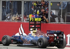 Job done: Webber's Red Bull team rush to congratulate him as he crosses the finishing line