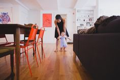 A documentary photograph of mother helping her baby walk during an in home lifestyle family photo session in Jamaica Plain - Boston, Massachusetts - Gina Brocker Photography