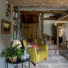 Flooring was laid in keeping with the period of the house, including stone flags and aged wooden boards. An armchair at the bottom of the stairs creates a welcoming look, while adding the owners' trademark zesty colour hits.