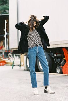 A striped t-shirt is paired with a black jacket, belted jeans, and white boots