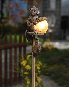 Sammy Squirrel Solar Outdoor Garden Stake Light - Things can get pretty squirrelly out there when Sammy goes to work lighting up your yard with his giant glowing acorn. Sammy is crafted of hand-painted polyresin and perches atop a wooden pole that stakes into the ground. His solar powered acorn lights up each evening to illuminate your yard.  Item #15169
