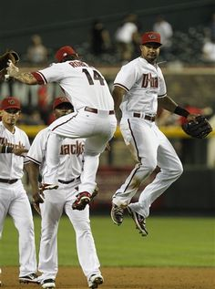 Arizona Diamondbacks' Ryan Roberts (14) and Chris Young, right, celebrate a win over the Pittsburgh Pirates as teammates Gerardo Parra, left, and Justin Upton look on after a baseball game Monday, April 16, 2012, in Phoenix. The Diamondbacks defeated the Pirates 5-1.