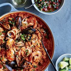 Chef Ricardo Zarate's peruvian arroz con mariscos is like an easy seafood paella. He starts with cooked rice and flavors the fish with vibrant red chile paste and tomato salsa. Get the recipe on Food & Wine.