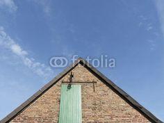 Spitzer Giebel einer alten Scheine aus Backstein  mit grüner Tür zwischen Helpup und Währentrup in Ostwestfalen-Lippe am Teutoburger Wald