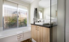 Stylish bathrooms with semi-inset vanity basins, mixer taps and glass semi-frameless pivot screen doors