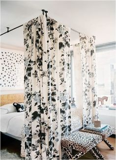 curtain rods hung from the ceiling to create a canopy bed