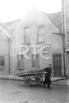 A man pulls a two-wheeled cart past a house on Marrowbone Lane, Dublin city, in 1952 or 1953. Note the cobblestones on the street. Collection RTÉ Johnson Collection Photographer Johnson, Nevill
