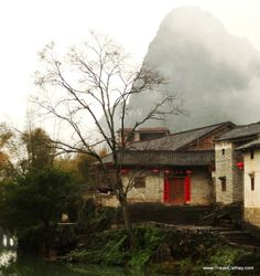 The ancient village of Huangyao with a mysterious fog enveloping the karst peak in the background. Guangxi province, China. #travel