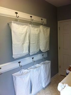 "This photo comes from an Amazon.com user: ""We bought 3""x1"" pine wood 6' long. Then added trim around each side. The bags are hung so they don't touch the floor thus we can mop and sweep under them. This as completely freed up floor space and organized our laundry room!"""