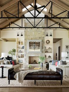 Located in Santa Rosa, California, this modern farmhouse's living room features a stone clad floor-to-ceiling fireplace and a tall vaulted ceiling.
