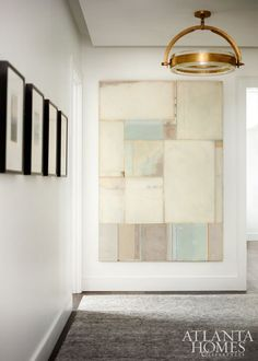 Barbara Westbrook's clients looked to procure works exclusively by Atlanta and Southern artists. In the hallway vestibule, a mixed-media work by Dusty Griffith, represented by Pryor Fine Art, is a soothing focal point. Coup d'Etat pendant through R Hughes. Rug by Moattar.