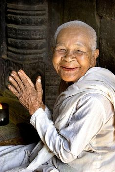 Nun at Bayon ~ a well-known and richly decorated Khmer temple at Angkor in Cambodia