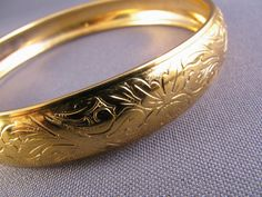 This is a lovely vintage 1960s gold plated etched bangle bracelet. The etched design is very beautiful (much prettier than the photos show)