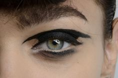 Simple shapes can often make a big statement. Black futuristic eyeliner and eyeshadow make-up.
