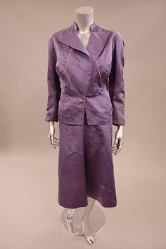 A Charles James couture violet cannelé silk suit, late 1930s, un-labelled, the jacket with angular neckline, pointed lapels with openings at the top, presumably for threading a scarf through, the curving front seams piped in white, the bias-cut skirt with notched waistline, lined with ivory crepe silk,