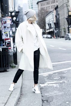 Vanessa Hong of The Haute Pursuit layers a long white coat over a white t-shirt and black leather pants combo with Adidas tennis shoes and a gray beanie