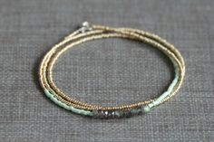 This pretty multi wrap bracelet features seed beads in shades of mint green and pale gold, with an inch of faceted labradorite rondelles in the