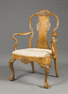 A George II walnut armchair circa 1740 with a carved feather motif cresting rail and C-scroll supports, shepherd`s crook arms, a bowfront upholstered drop-in seat, carved apron, carved knees with feather motif and raised on carved claw and ball supports Sotheby's