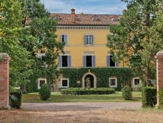 This preserved 17th-Century villa in Italy has yellow stucco walls, Spanish tile roofing, blue shutters, dormer windows, multiple chimneys and an arched entry with ivy growing all around.