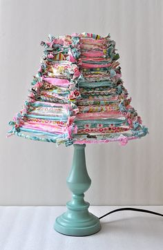 Love this! Just tie strips of ripped material to a lamp shade frame and voila...you have this adorable lamp. Could be altered for boy or girl colors!!
