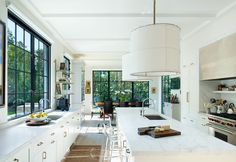The white surfaces of the kitchen reflect the light brought into the space through the large windows. The shallow beams on the ceiling create a subtle texture and rhythm. The kitchen opens into an equally spacious dining room. Outdoor Decor, Home Decor, Homemade Home Decor, Interior Design, Decoration Home, Home Interiors, Home Decoration, Interior Decorating, Home Improvement