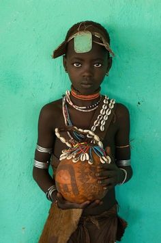 Africa. Young Hamer girl, decorated gourd with cowrie shell decor, Ethiopia by Alison Wright.