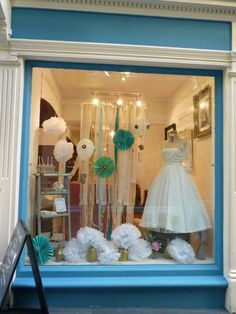 Wedding 'cloud 9' white vintage shop window display. Pom poms and hot air balloons!
